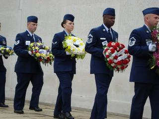Each wreath carrier holds an organization's wreath and has an identifying number clipped to their jacket.
