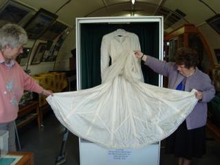 Sue and Marlene show Helen McMullen's parachute wedding dress